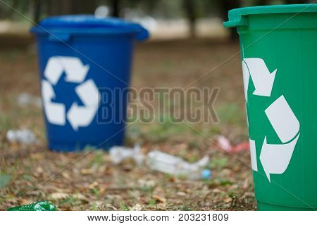 A close-up of a couple of bright blue and green recycling bins in the park. Plastic rubbish containers next to plastic bottles on a blurred natural background. Environment, ecology, recycling concept.
