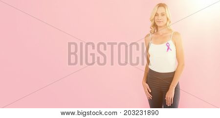 Portrait of young woman with breast cancer awareness ribbon against pink background