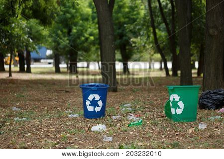 A couple of bright blue and green recycling bins in the park. Plastic rubbish containers next to plastic bottles on a blurred natural background. Environment, ecology, recycling, pollution concept.