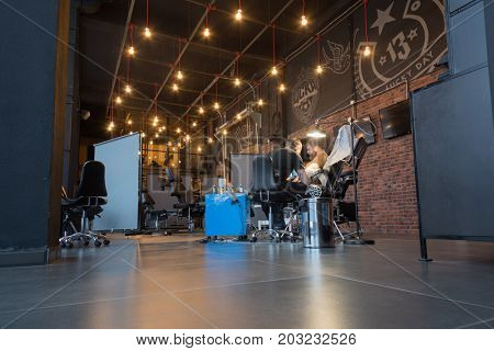 MOSCOW - JAN 23, 2017: Tattoo master and client in tattoo parlor in Illskill, New Illskill complex includes car service, hookah, restaurant, barbershop and tattoo parlor