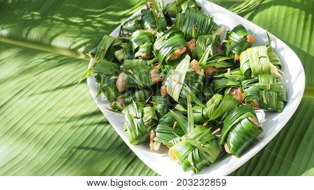 Chicken wrapped pandan raw for fried of Thai food background is banana leaf Nice shot of nature concept idea of green to save world has a copy space.