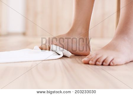 Foot correction gymnastics. The child with bare feet performs corrective gymnastic exercises.