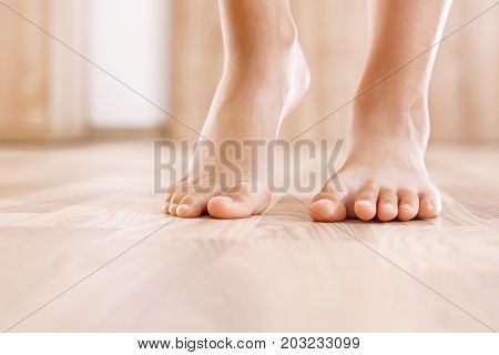 Healthy foot baby. Feet of baby's naked against the background of the wooden floor