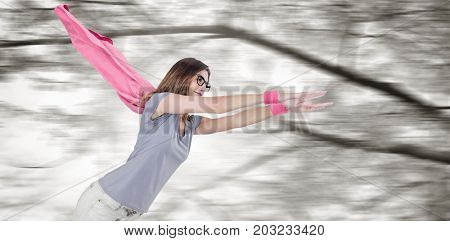 Woman in superhero costume pretending to fly  against low angle view of flowering tree