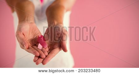 Mid section of woman with pink ribbon breast cancer awareness ribbon