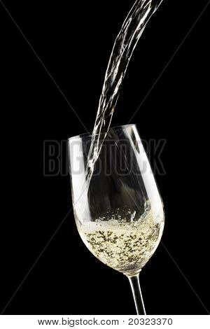 White wine being poured into a wine glass on a black background
