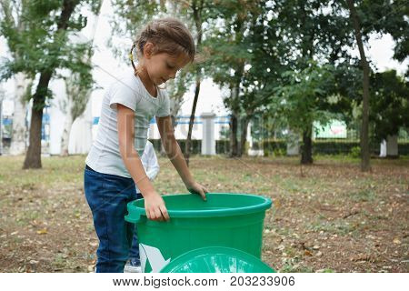 A close-up portrait of a beautiful girl holding a big green recycling container. A little child throwing out the plastic trash in the bin on a blurred park background. Ecology, nature pollution concept.