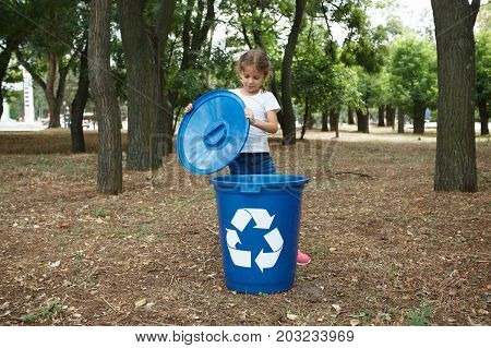 A full-length portrait of a beautiful little girl opening a bright green recycling container. A child collecting the garbage on a blurred park background. Ecology, nature pollution concept.