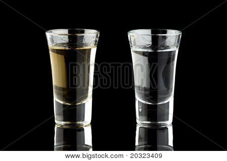 Two shots of tequila isolated on a black background