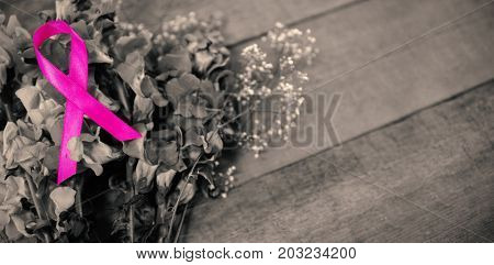 High angle view of pink Breast Cancer Awareness ribbon on flowers over wooden table