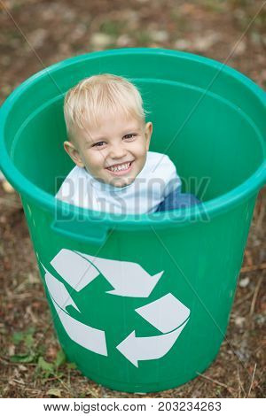 A close-up portrait of a blond child sitting in a bright green recycling container. Child hiding in the plastic bin on a blurred park ground background. Ecology, nature pollution, childhood concept.