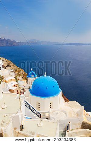 view of caldera with classical blue church domes, Oia, Santorini