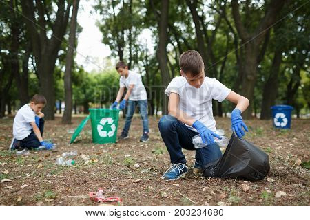 A full-length portrait of a boy sitting on a ground and collecting rubbish items from the ground. Child picking up the plastic trash on a blurred natural background. Ecology, nature pollution concept.