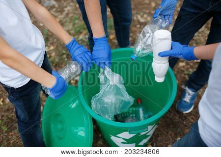 A close-up picture of child's legs and hands in blue latex gloves. A group of schoolers throwing out the plastic trash in a green recycling bin. Environment, ecology, nature pollution concept.