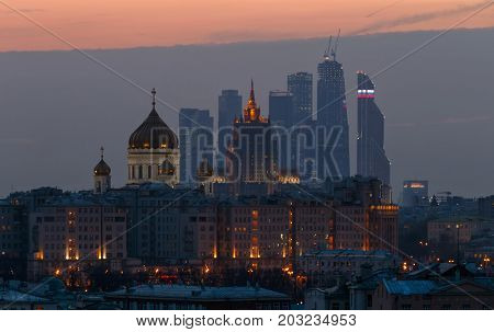 MOSCOW - MAR 19, 2015: Domes of church and Moscow International Business Center during evening