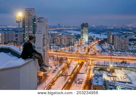 MOSCOW - NOV 10, 2016: Man sits on high skyscraper rooftop near beacon light at winter night