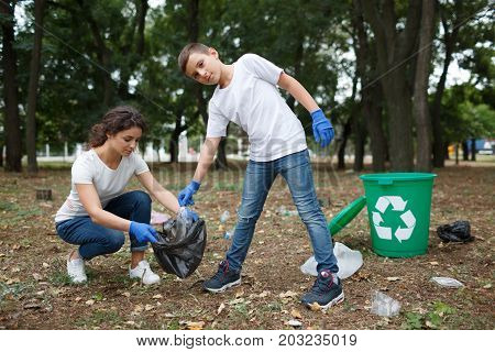 A full-length portrait of a child and a young woman in blue latex gloves. A family picking up the plastic trash and putting it in a black garbage bag on a blurred park background. Pollution concept.