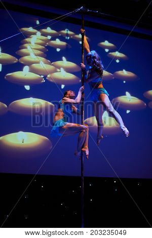 MOSCOW, RUSSIA - FEB 11, 2017: Two girl perform against background with burning candles on stage of Korolevskiy concert hall during Pole Dance Show. Concert hall is designed for 750 spectators.