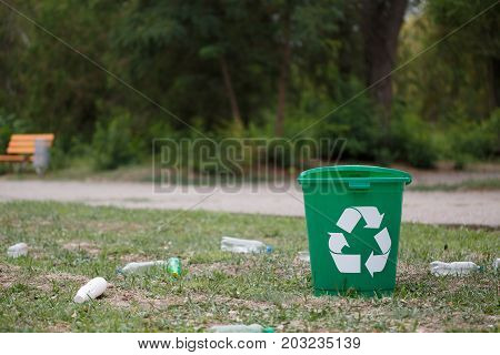 A plastic garbage bin with a recycling sign next to plastic bottles on a blurred natural background. A bright green recycling bin in the park. Ecology, environment, pollution concept.