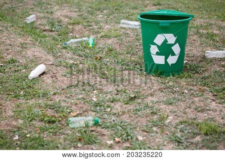 A colorful green recycling bin standing in the field. A plastic recycling container for garbage next to plastic bottles on a blurred ground background. Ecology, nature protection concept.