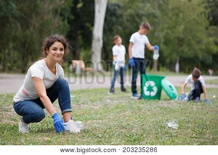 A full-length portrait of an attractive young woman sitting and collecting plastic trash. A young beautiful ecologist picking up a plastic bottle on a blurred park background. Pollution concept.