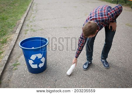 A guy in a checked shirt takes care about the nature. A male hand picking up a white plastic bottle from the ground to put it into the recycling container. Ecology, pollution, nature concept.