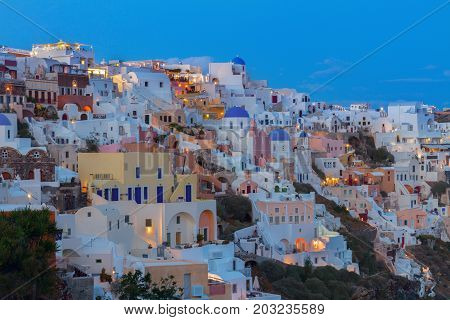houses of Oia village at night, Santorini, Greece.