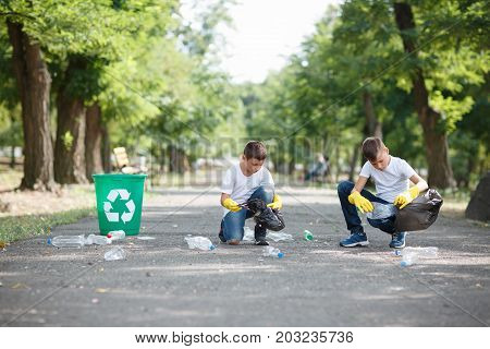 A couple of children sitting and collecting the plastic trash on a blurred park background. Two ecologists in yellow latex gloves. Environment, ecology, pollution concept. Copy space.
