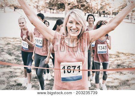 Portrait of happy female winner of breast cancer marathon race at park