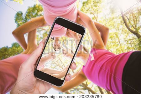 Hand holding mobile phone against white background against volunteer women forming huddle