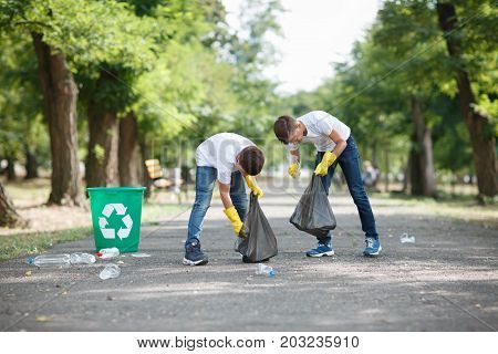 A full-length portrait of children collecting the plastic trash. A couple of children in yellow latex gloves on a blurred park background. Environment, ecology, pollution concept. Copy space.