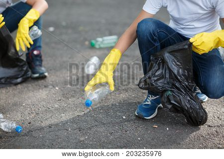 A close-up picture of children's legs and hands in yellow latex gloves. Children picking up the plastic trash. Environment, ecology, nature protection, pollution concept. Copy space.