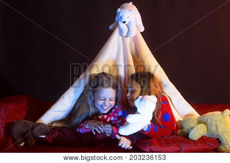 Girls With Happy Faces Lie Under Blanket Tent