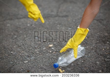Ecologists picking up the plastic bottle. A close-up picture of hands in yellow latex gloves. Collecting the garbage in the park. Environment, ecology, nature protection, pollution concept. Copy space.
