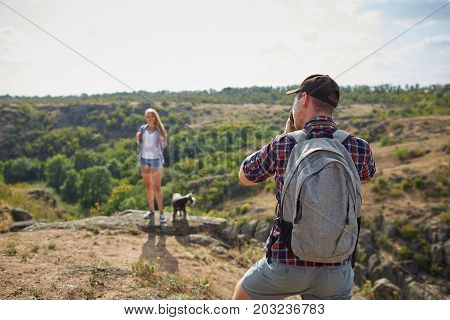 A close-up picture of a professional photo-shooting process on a natural background. A portrait of a tourist taking a photo of his girlfriend with a dog. Tourism, photography, nature concept.