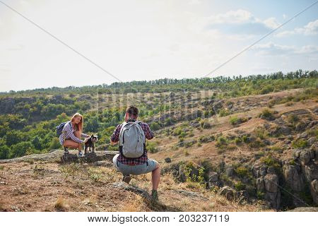 A full-length portrait of a sitting tourist taking a photo of his girlfriend with a dog. Professional photo-shooting process on a natural background. Tourism, photography, nature concept. Copy space.