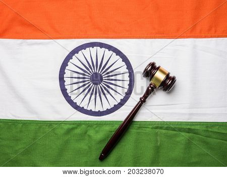 stock photo showing Indian low and jurisdiction - Indian national flag or tricolour with wooden gavel showing concept of law in India