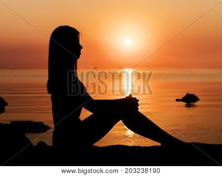 Sunset, sexy woman silhouette. Vacation, sillhouette of traveling girl bikini sitting on sand beach in sunrise or sunset. Lady with slim sexy body on tropical beach. Luxury destination