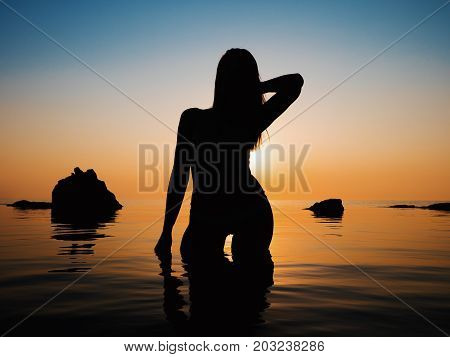 Sunset, sexy woman silhouette. Vacation, sillhouette of traveling girl in bikini standing in sea at sunrise or sunset. Lady with slim sexy body on tropical beach. Luxury destination