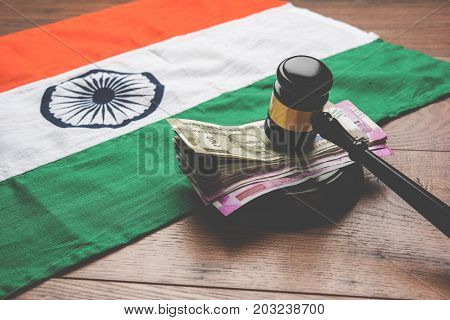 stock photo of Indian Currency Rupee Notes with Law Gavel isolated on white, concept showing indian finance law with paper currency of 500,2000 with gavel and indian flag