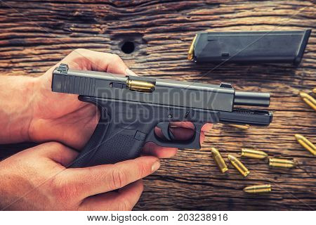 Charging gun. Man hands charging 9mm pistol gun.