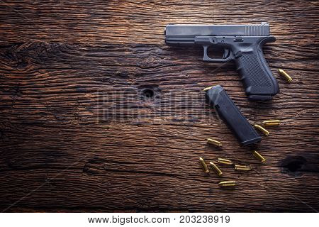 Gun pistol. 9 mm pistol gun and bullets strewn on the rustic oak table.