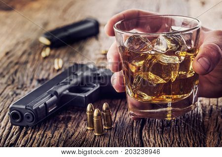 Gun and alcohol. 9mm pistol gun and cup whiskey cognac or brandy.