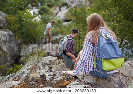 A back view of a small group of travelers climbing down the rocky hill outdoors. Tired company of young people on a blurred natural background. Nature, friendship, adventure concept.