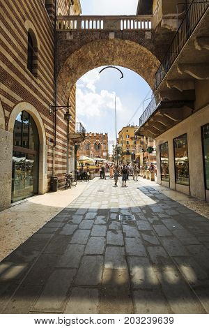VERONA ITALY - JUNE 25 2016: Entrance of the Piazza dei Signori with tourists and shop windows in a sunny day with clouds. Verona Italy.