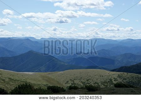 A mountain landscape shot from one of the peaks. Blue mountains to the horizon and the sky with clouds. Chamar-Daban (Khamar-Daban) montains Siberia Russia. Summer day.