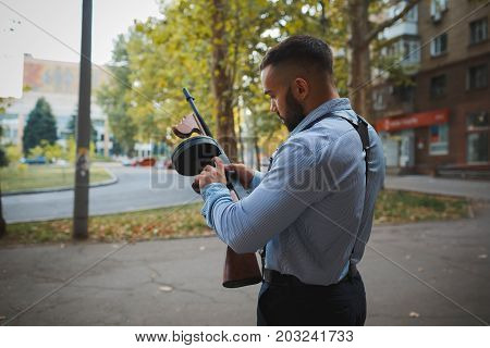 A back view of a dangerous gangster man in classic clothes with a rifle. A handsome secret agent with a beard reloading his weapon on an urban background. Danger, gangster concept. Copy space.