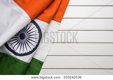 stock photo of folded indian flag kept over table with copy space