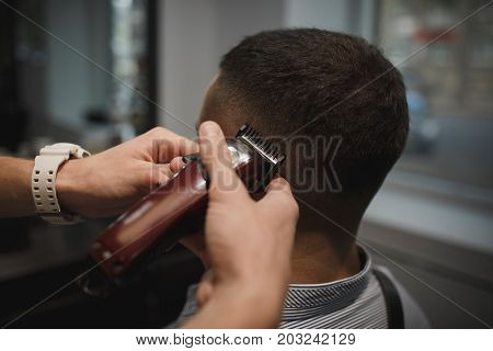 Close-up picture of a shaving process on a blurred background. Back view of hairdresser's hands shaving male client's head. Hairstylist serving a client at barbershop. Beauty, style, hipster concept.