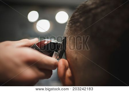 Macro picture of a shaving process on a blurred background. Back view of hairdresser's hands shaving male client's head. Hairstylist serving a client at barbershop. Beauty, style, hipster concept.